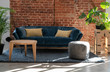Leinwanddruck Bild - Navy sofa with plants in bright industrial interior of living room with bricky wall with copy space. Loft apartment.