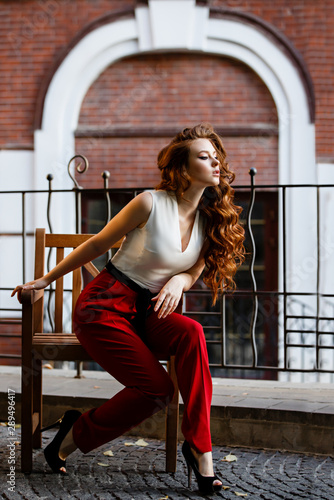 Young curled girl weared in classic trouser jumpsuit on background of old City Tablou Canvas