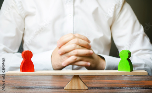 Photo A man with hands in the lock and looks at the scales with green and red figures