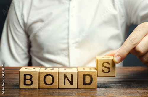 Fotografiet Businessman puts wooden blocks with the word Bonds