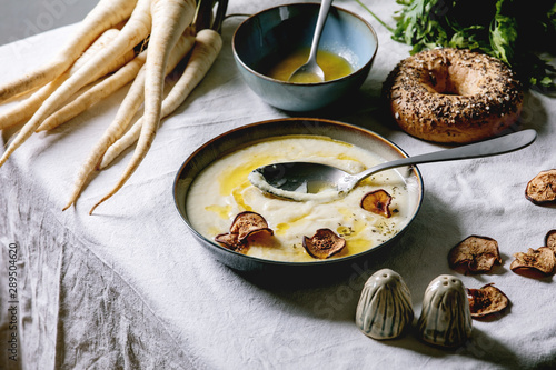 Cuadros en Lienzo Parsnip cream soup in ceramic bowl with butter sauce, sun dried pears, bundle of