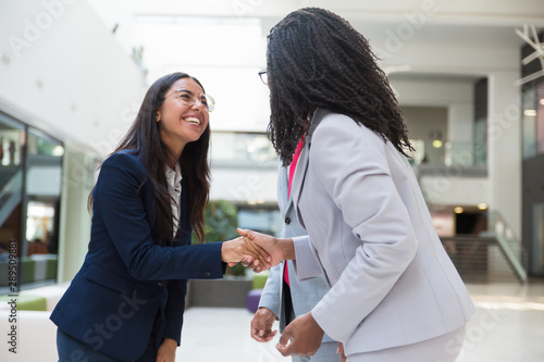 Happy excited diverse business partners greeting each other in hallway. Business women standing in office hall, shaking hands with each other, smiling and laughing. Multiethnic communication concept