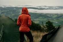 Back View Of Girl Tourist In Orange Jacket Looking At Beautiful Scenery Of Mountains