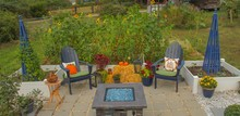 Outdoor Patio And Raised Garden Beds At Sunset, Decorated For Autumn With Pumpkins, Plants, Hay Bales, Chrysanthemum And Lanterns