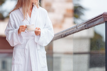 Charming Healthy Young Blonde Woman With A Cup Of Coffee In A Bathrobe Walks Barefoot On Her Large Terrace Enjoying The Summer Nature. Concept O Vacation In Own Big Country House Or Hotel