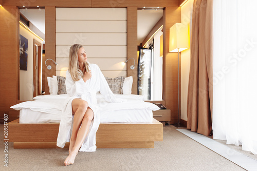 Deurstickers Ontspanning Beautiful contented young woman is relaxing at resort in SPA hotels and sitting on bed with bathrobe and towel after treatment procedures. Concept of travel to therapeutic spa hotels for millennials