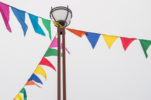 Colorful Triangular Cloth Flags Hanging On Ropes Tied To A Lamppost, Decoration For Festival, Carnival, Holiday