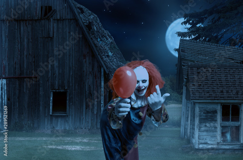 Stampa su Tela eerie clown with a balloon in hand in front of a scary scene