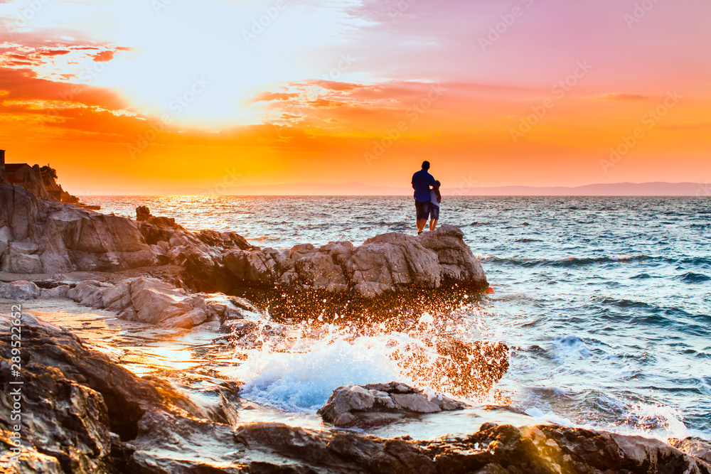 Fototapety, obrazy: Yung man standing on a rock and looking at the sea sunset