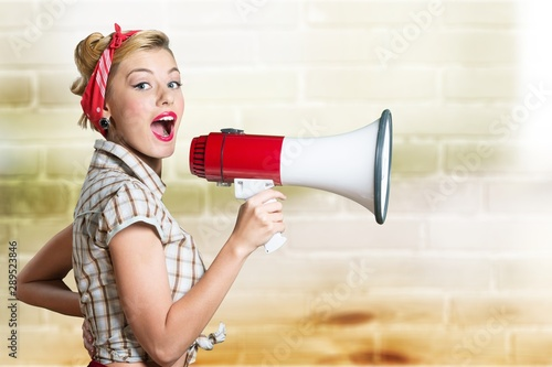 Portrait of woman holding megaphone, dressed in pin-up style - 289523846
