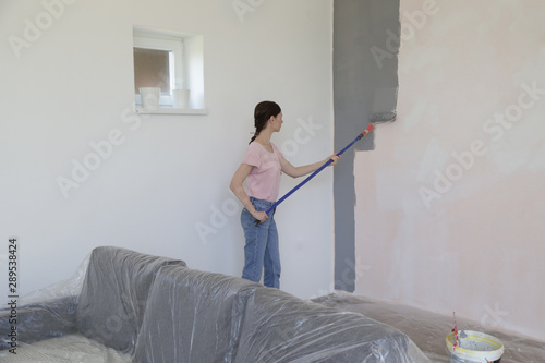 Fotomural Woman painting with gray paint over a white wall