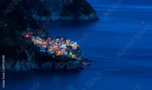 Staande foto Liguria The fishing village of Manarola in Cinque Terre, Italy, illuminated at dusk during blue hour with the Mediterranean sea as background
