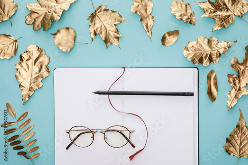flat lay with autumnal golden foliage near blank notebook with glasses on blue background