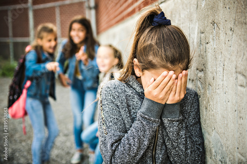 Photo  A sad girl intimidation moment on the elementary Age Bullying in Schoolyard