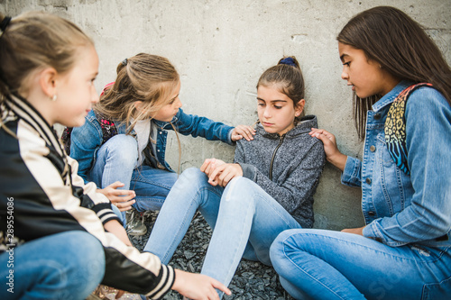Obraz na plátně girl problem at school, sitting and consoling child each other
