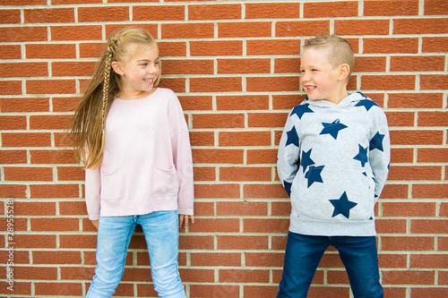 Fotografie, Obraz  Young Schoolgirl and boy standing against brick school wall
