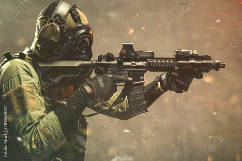 Fotografiet Elite special unit soldier with gasmask is holding assault rifle and aiming at t