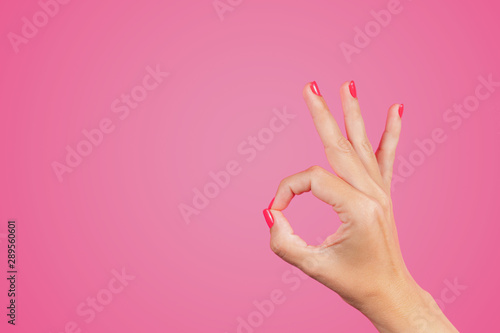 Closeup view of beautiful white female hand isolated on pink background Poster Mural XXL