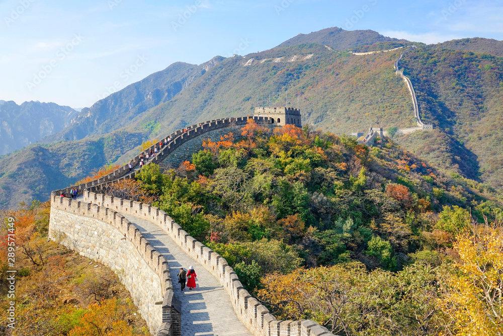 Fotografie, Obraz Tourists walk along the ancient Great Wall of China on a sunny autumn day