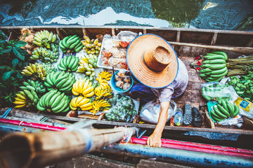 floating market - top view of boat full of fresh fruits on sale