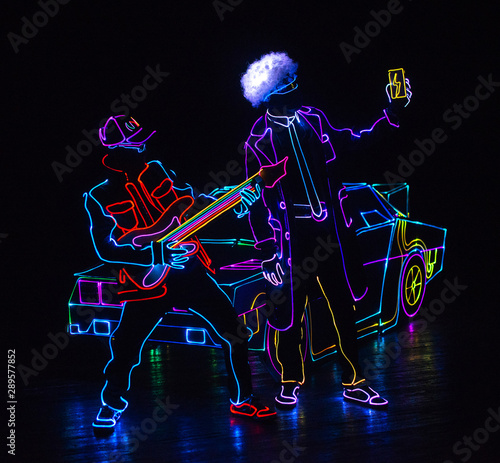 dancers in led suits on dark background, colored show - 289577852
