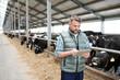 Leinwandbild Motiv Mature male worker of contemporary animal farm using digital tablet