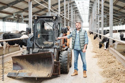 Obraz Mature confident worker of modern farmhouse standing by working equipment - fototapety do salonu