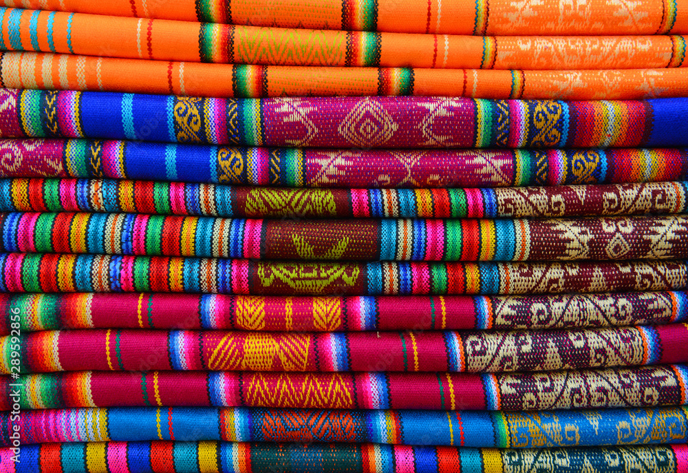 Fototapety, obrazy: A pile of colorful traditional textiles in the Andes mountain range sunday market of Otavalo, north of Quito, Ecuador.