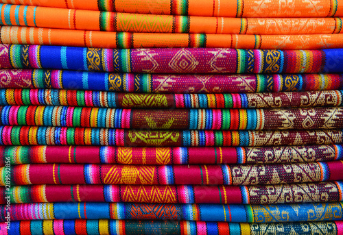 A pile of colorful traditional textiles in the Andes mountain range sunday market of Otavalo, north of Quito, Ecuador.