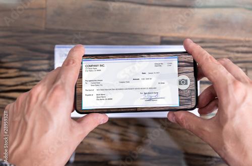 Fototapeta Man Taking Photo Of Cheque To Make Remote Deposit obraz