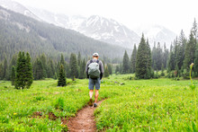 Open Valley With Man Walking In Rain On Conundrum Creek Trail In Aspen, Colorado In 2019 Summer On Cloudy Day And Dirt Road