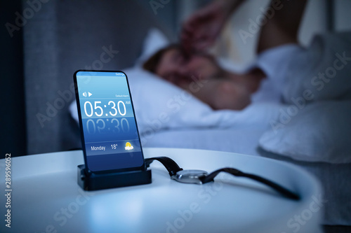 Obraz Man Waking Up With Alarm On Mobile Phone - fototapety do salonu
