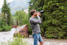 Man Taking Photos With Camera In Redstone, Colorado During Summer With Large Boulder And Red Bridge On Crystal River By Trees