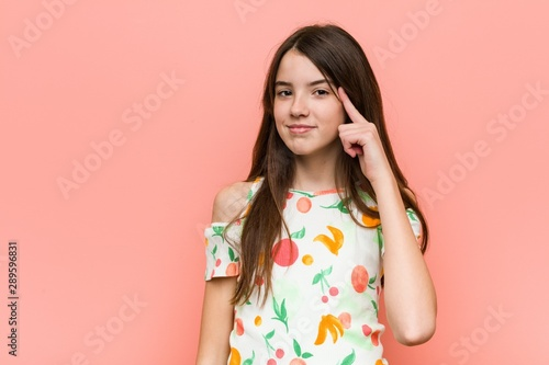 Fotomural  Girl wearing a summer clothes against a red wall pointing temple with finger, thinking, focused on a task