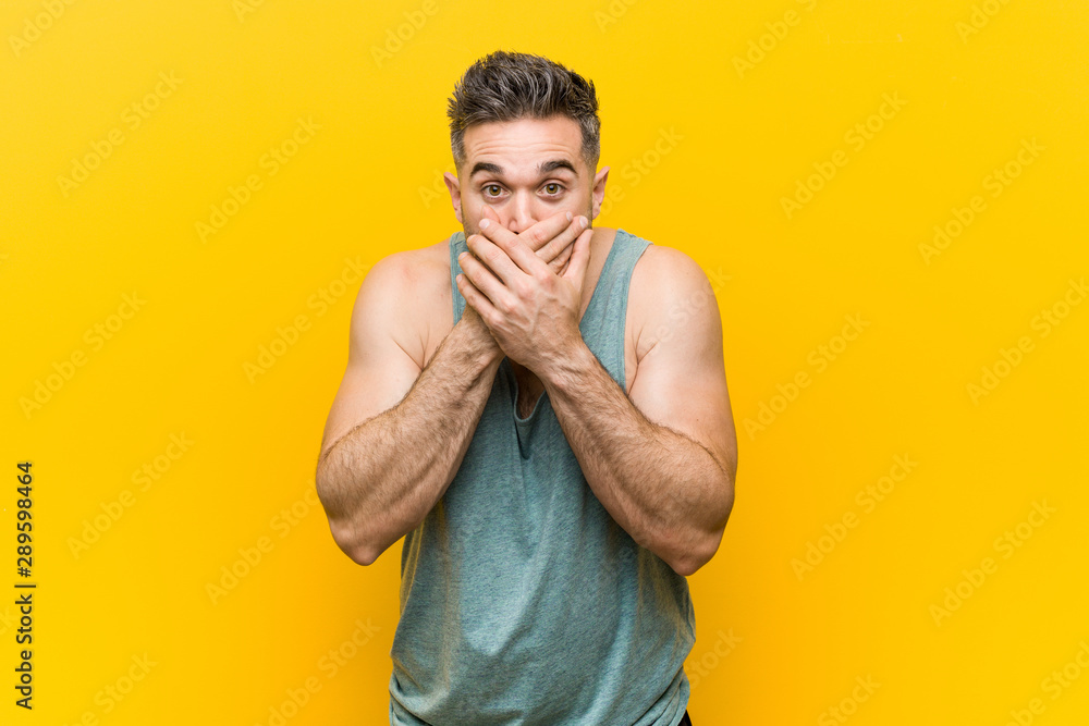 Fototapety, obrazy: Young fitness man against a yellow background shocked covering mouth with hands.