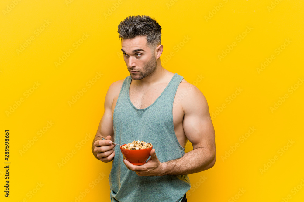 Fototapeta Caucasian man holding a cereal bowl smiling confident with crossed arms.