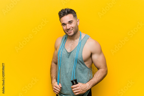 Stampa su Tela  Caucasian man holding a jump rope happy, smiling and cheerful.