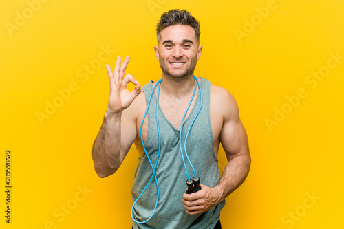 Fototapeta  Caucasian man holding a jump rope cheerful and confident showing ok gesture