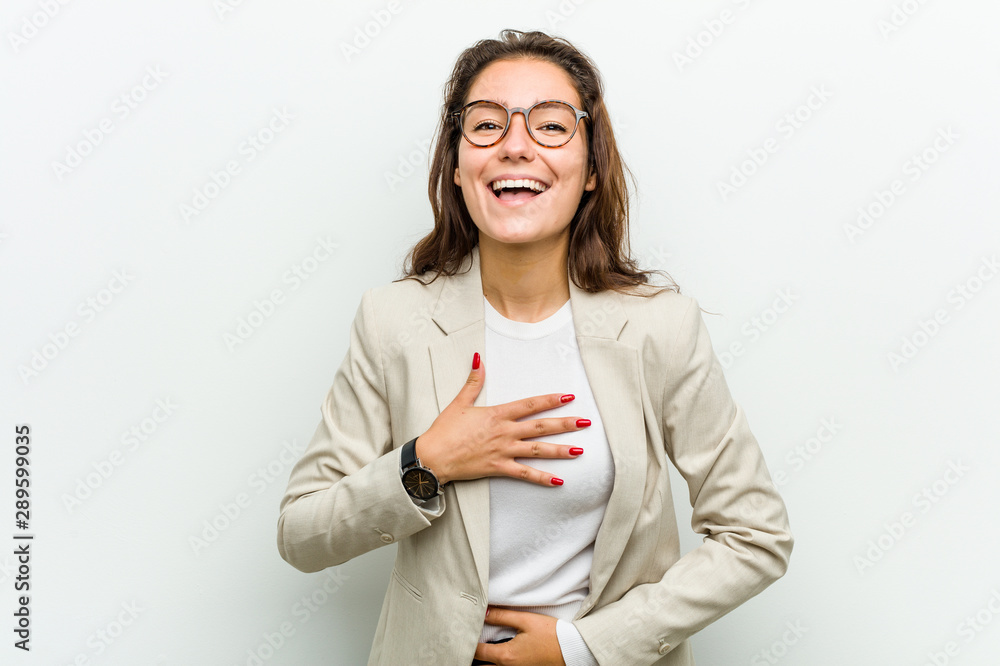 Fototapeta Young european business woman laughs happily and has fun keeping her hands on stomach.