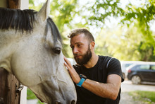 A Bearded Man Petting His Handsome White Horse On A Farm
