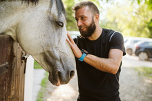 Summer Day On The Farm. Young Man Caress Horse