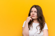 Leinwanddruck Bild - Young curvy plus size woman looking sideways with doubtful and skeptical expression.
