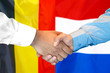 canvas print picture - Business handshake on the background of two flags. Men handshake on the background of the Belgium and Dutch flag. Support concept
