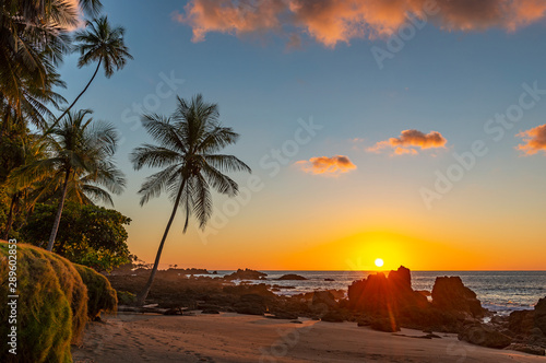 Sunset along the volcanic rock beach of Corcovado national park with a sunbeam by the Pacific Ocean, Costa Rica, Central America Wallpaper Mural