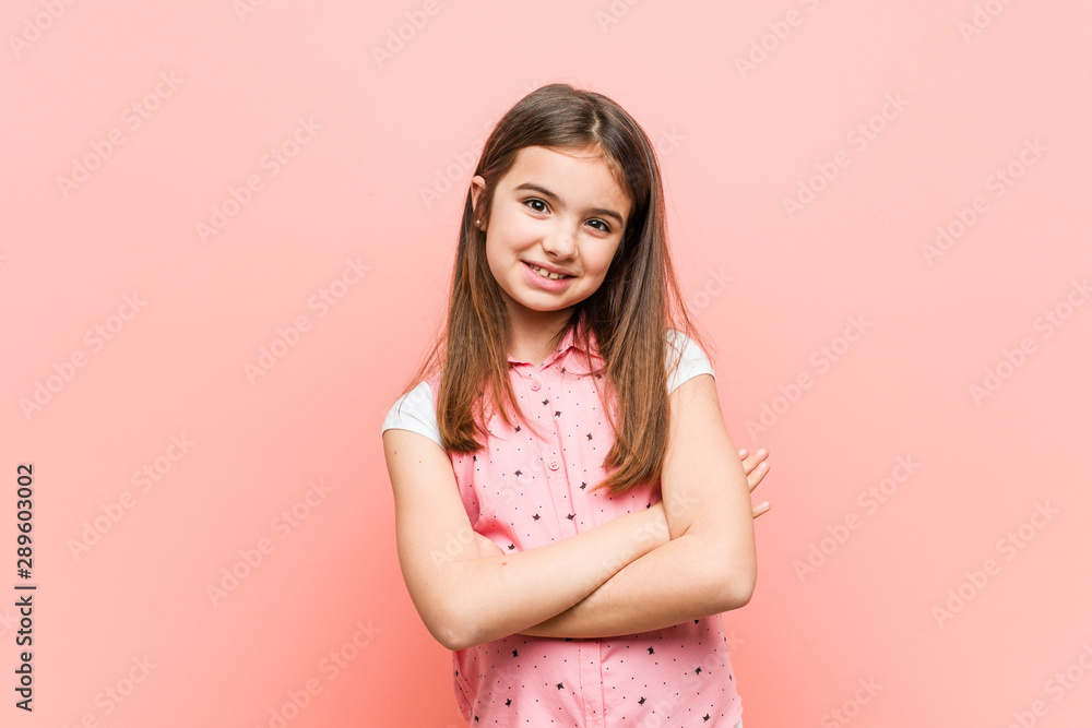 Fototapeta Cute little girl who feels confident, crossing arms with determination.