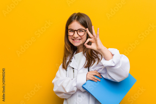 Fotomural  Little caucasian girl wearing a doctor costume cheerful and confident showing ok gesture