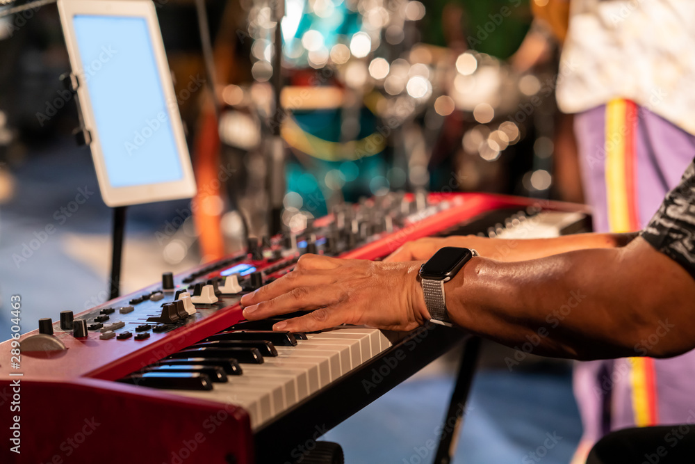 Fototapeta Pianist playing red electric piano in concert at night.
