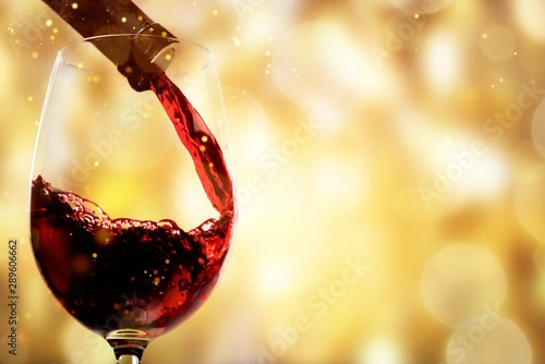 Vin Red wine being poured in wineglass, closeup