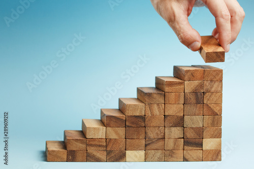 Fotomural  hand put wooden blocks arranging stacking for development as step stair