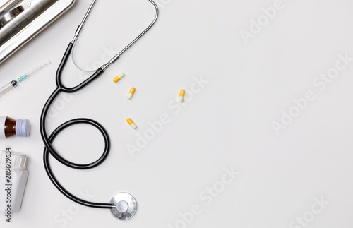 Fototapeta Creative flatlay of doctor medical equipment white table with stethoscope, medical documents, thermometer, syringe and pills, Health care concept, Top view with copy space, Isolated on white obraz
